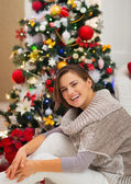 Portrait of happy young woman sitting near Christmas tree — Stockfoto