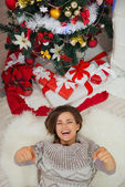 Happy woman laying near Christmas tree and pointing in camera — Stock Photo