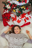 Happy woman laying near Christmas tree. Upper view — Stock Photo