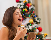 Smiling young woman in pajamas eating cookies with hot chocolate — Stock Photo