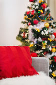 Closeup on sofa with red pillow in front of Christmas tree — Stock Photo