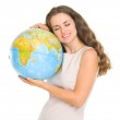 Happy young woman hugging globe — Stock Photo #21517577