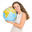 Happy young woman hugging globe — Stock Photo