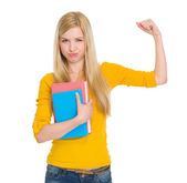 Happy student girl with book showing biceps — Stock Photo