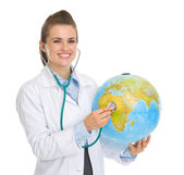 Happy medical doctor woman listening globe with stethoscope — Stock Photo