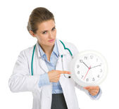 Medical doctor woman pointing on clock — Stock Photo