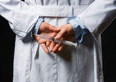 Closeup on medical doctor woman hiding syringe behind back — Stock Photo