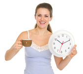 Young woman in pajamas with cup of coffee and clock — Stock Photo