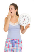 Young woman in pajamas with clock yawing after sleep — Stock Photo