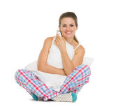 Young woman in pajamas sitting with pillow — Stock Photo