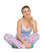 Young woman in pajamas sitting on floor — Stock Photo