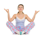Young woman in pajamas sitting on floor and meditating — Stock Photo