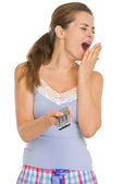 Young woman in pajamas with TV remote control yawing — Stock Photo