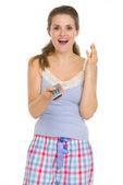 Mujer joven en pijamas con tv con control remoto — Foto de Stock