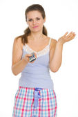 Young woman in pajamas holding TV remote control — 图库照片