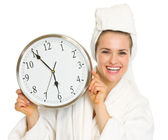 Young woman in bathrobe showing clock and thumbs up — Stock Photo