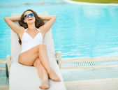 Young woman in swimsuit relaxing on chaise-longue — Stock Photo