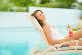 Young woman relaxing in pool with cocktail — Stock Photo