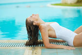 Young woman relaxing in poolside — Stock Photo