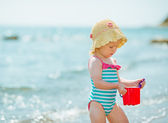 Baby playing with pail near sea — Stock Photo