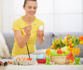 Zbliżenie na stole z ozdoba wielkanocna i kobieta rysunek na jajko — Zdjęcie stockowe