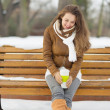 Happy young woman sitting on bench with hot beverage in winter o - Stock Photo