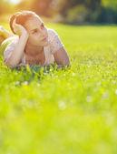 Thoughtful girl laying on meadow — Stock Photo