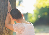 Girl looking out from tree. Rear view — Stock Photo