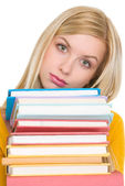 Frustrated student girl holding stack of books — Stock Photo