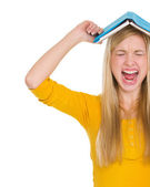 Angry student girl with book over head — Stock Photo