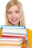 Happy student girl holding stack of books — Stock Photo