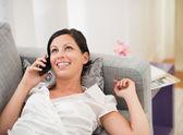 šťastná mladá žena na gauči a mluví mobilní telefon — Stock fotografie