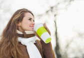 Happy young woman drinking hot beverage in winter park — Stock Photo