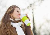Šťastná mladá žena pije horký nápoj v zimě parku — ストック写真