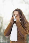 Woman blowing nose in winter outdoors — Stock Photo
