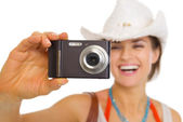 Closeup on camera in hand of young beach woman in hat — Stock Photo