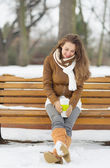 Happy young woman sitting on bench with hot beverage in winter o — Stock Photo