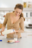 Happy young woman pouring milk into glass — Stock Photo