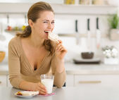 Young woman eating snacks in modern kitchen — Stock Photo