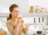 Young woman eating crisp bread with milk and looking on copy spa — Stock Photo