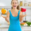 Happy young woman juggling with bell peppers in kitchen — Stock Photo