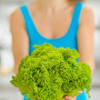 Closeup on green salad in hand of young woman — Stock Photo #23411112