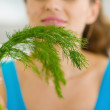 Closeup on young woman smelling fresh dill — Stock Photo #23411186