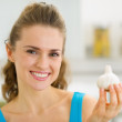 Smiling young housewife showing garlic — Stock Photo #23411300