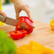 Closeup on housewife cutting red bell pepper on cutting board — Stock Photo #23411826