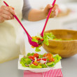 Closeup on woman putting fresh vegetable salad into plate — Stock Photo