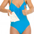Closeup on young woman in swimsuit showing air tickets and thumb — Stock Photo #23414180