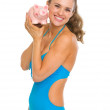 Happy young woman in swimsuit showing piggy bank — Stock Photo #23414210