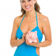 Smiling young woman in swimsuit holding piggy bank — Stock Photo #23414228
