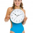 Happy young woman in swimsuit showing clock — Stock Photo #23414240